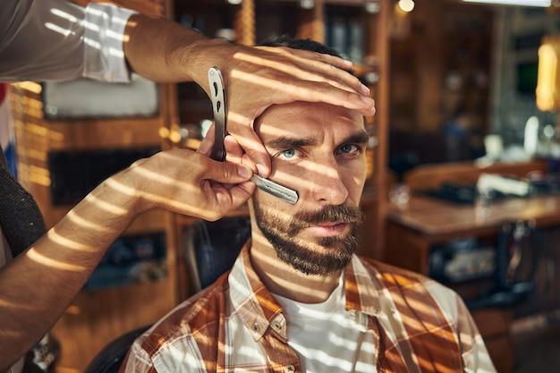 Jeune homme barbu sévère ayant un barbier raser sa barbe avec un rasoir droit dans un salon de coiffure
