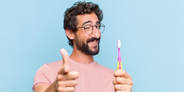 Jeune homme barbu souriant avec une attitude positive, réussie et heureuse, pointant vers la caméra, faisant signe des armes à feu avec les mains
