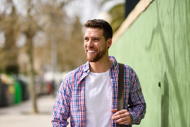 Jeune homme barbu souriant en contexte urbain. concept de style de vie.