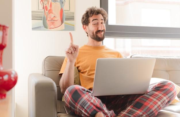 Jeune homme barbu souriant fièrement et en toute confiance faisant le numéro un pose triomphalement se sentant comme un leader et assis avec un ordinateur portable