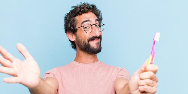 Jeune homme barbu souriant joyeusement donnant un câlin de bienvenue chaleureux, amical, aimant, se sentant heureux et adorable