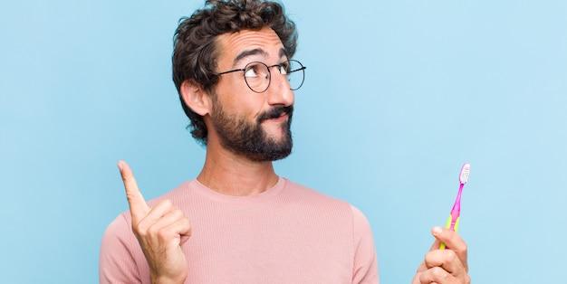 Jeune homme barbu souriant joyeusement et regardant de côté, se demandant, pensant ou ayant une idée