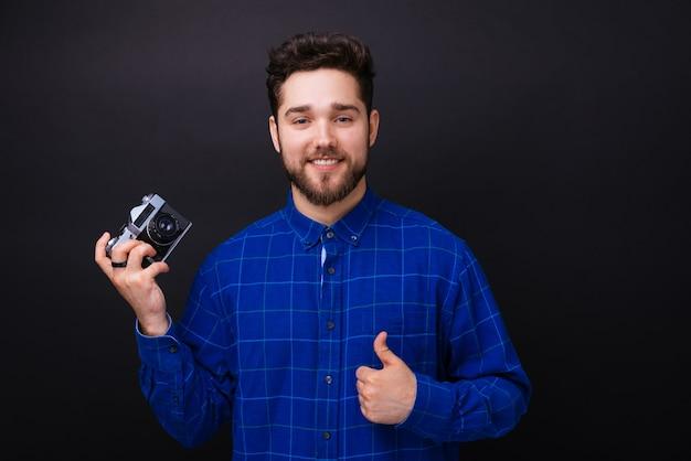 Jeune homme barbu souriant montrant un vieil appareil photo et le pouce vers le haut.
