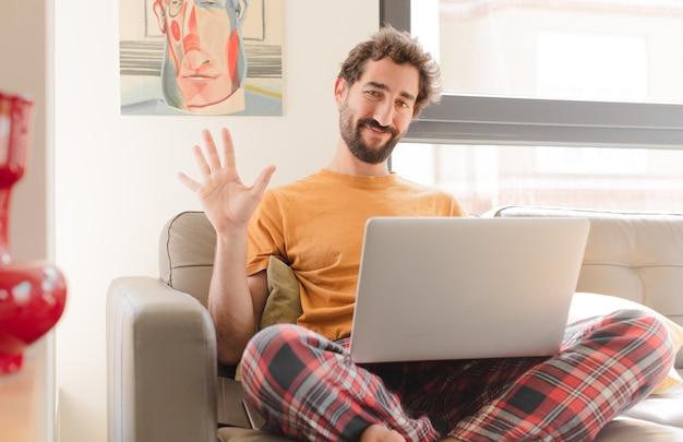 Jeune homme barbu souriant et à la recherche amicale montrant le numéro cinq ou cinquième avec le compte à rebours et assis avec un ordinateur portable