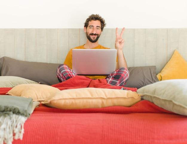 Jeune homme barbu souriant et à la sympathique montrant le numéro deux ou seconde avec la main en avant compte à rebours