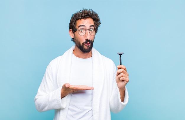 Jeune homme barbu à la surprise et choqué, avec la mâchoire tombée tenant un objet avec une main ouverte sur le côté