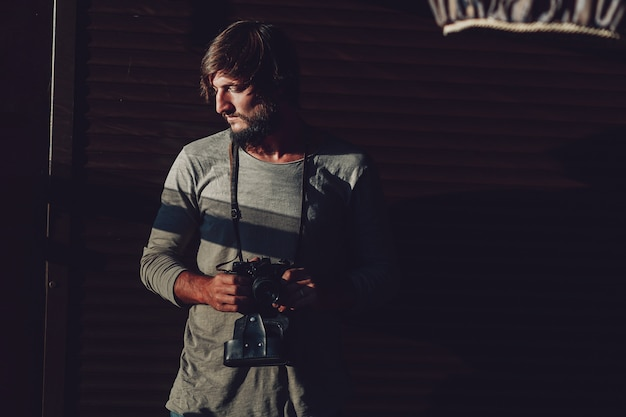 Jeune homme barbu en sweat gris, tenant une caméra et regardant de côté