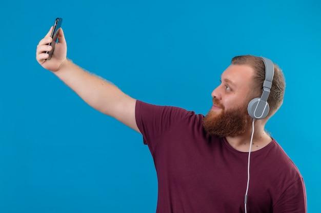Jeune homme barbu en t-shirt marron avec un casque prenant selfie à l'aide de son smartphone