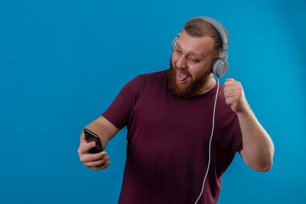 Jeune homme barbu en t-shirt marron avec des écouteurs prenant selfie à l'aide de son smartphone faisant grimace qui sort la langue