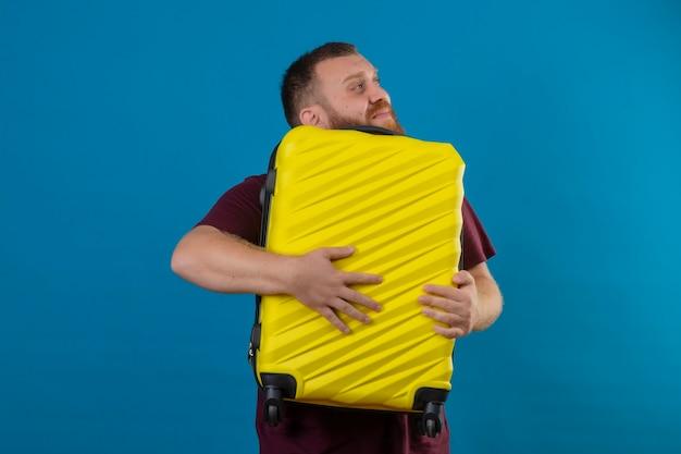 Jeune homme barbu en t-shirt marron tenant une valise de voyage à côté avec un look de rêve