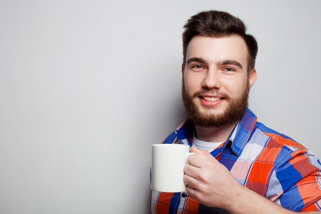 Jeune homme barbu avec une tasse de café