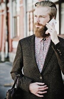 Jeune homme barbu avec téléphone portable, en plein air