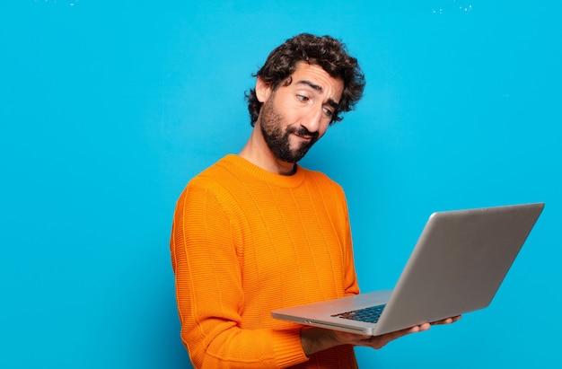 Jeune homme barbu tenant un ordinateur portable