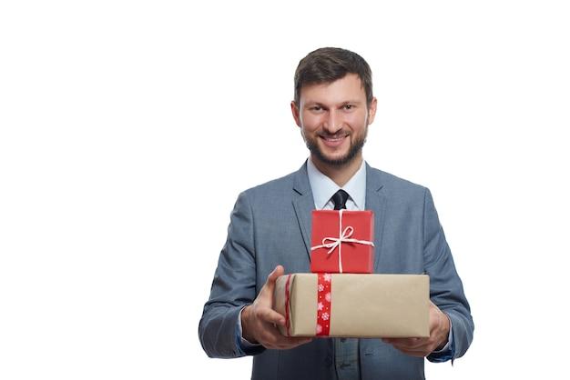 Jeune homme barbu tenant présente présente souriant à la caméra debout sur la surface de fond blanc.