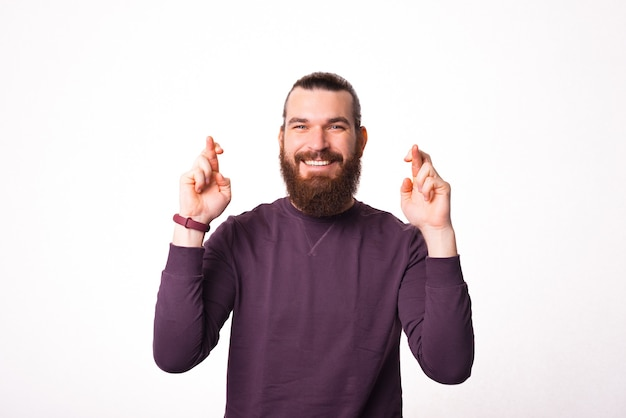 Jeune homme barbu tenant ses mains avec les doigts croisés en espérant que son rêve deviendra réalité