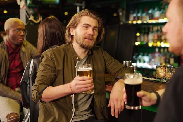 Jeune homme barbu en tenue décontractée buvant de la bière au comptoir du bar tout en regardant son ami devant la caméra et en lui parlant