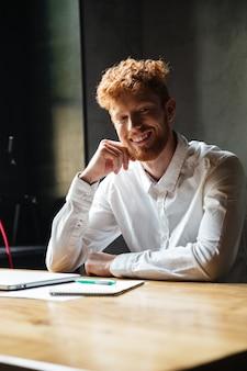 Jeune homme barbu tête de lecture gaie en chemise blanche, assis sur son lieu de travail