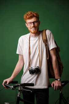 Jeune homme barbu de tête de lecture heureux avec sac à dos et appareil photo rétro