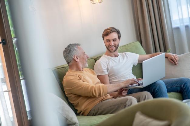 Jeune homme barbu travaillant sur un ordinateur portable, son père assis à côté de lui