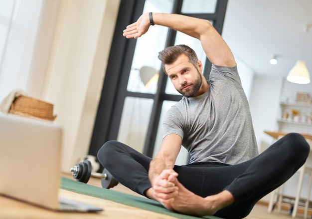 Jeune homme barbu utilisant un ordinateur portable et faisant de la gymnastique matinale