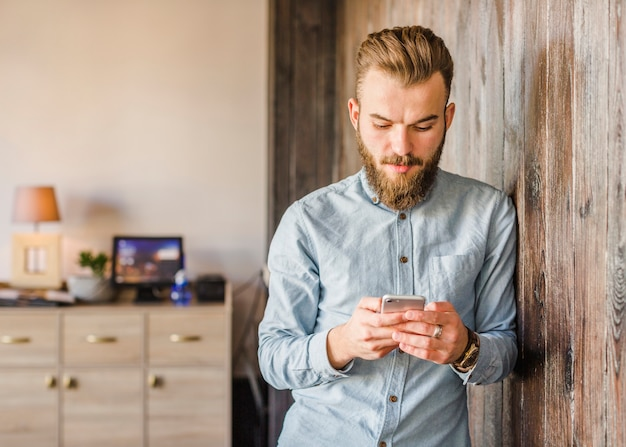 Jeune homme barbu utilisant un téléphone portable à la maison