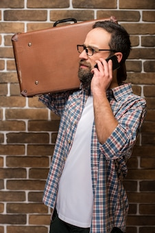 Jeune homme barbu avec une valise à l'épaule.