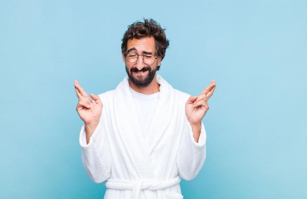 Jeune homme barbu vêtu d'un peignoir souriant et croisant anxieusement les deux doigts, se sentant inquiet et souhaitant ou espérant avoir de la chance