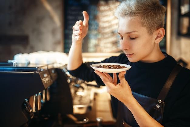 Jeune homme barista renifle des grains de café frais