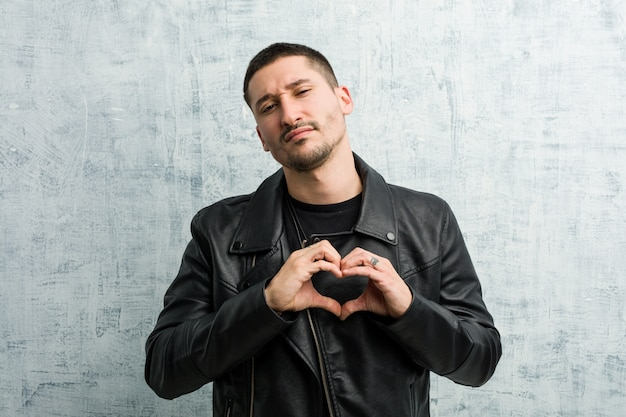 Jeune homme à bascule souriant et montrant une forme de coeur avec ses mains.