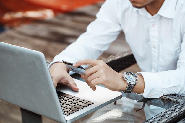 Le jeune homme beau aime faire des achats en ligne sur un téléphone mobile avec une carte de crédit.