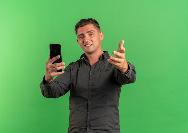 Jeune homme beau blond confiant tient le téléphone et tend la main à la caméra isolée sur fond vert avec espace de copie