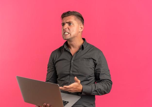 Jeune homme beau blond furieux tient et pointe sur ordinateur portable à côté isolé sur fond rose avec copie espace