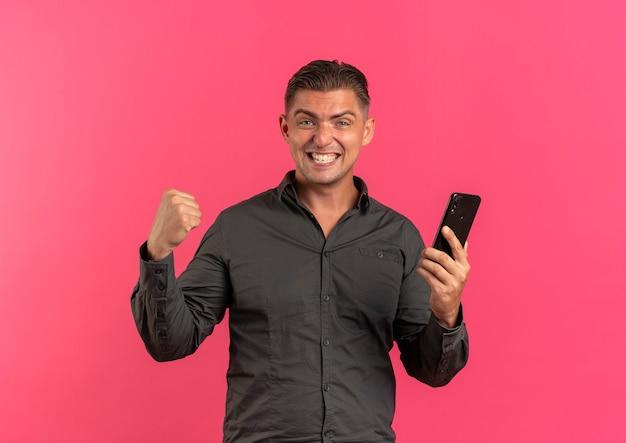 Jeune homme beau blond joyeux tient le téléphone et garde le poing en regardant la caméra isolée sur fond rose avec espace de copie