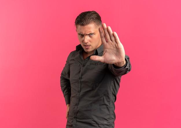 Jeune homme beau blond sérieux gestes arrêt signe de la main isolé sur fond rose avec espace de copie