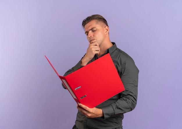 Jeune homme beau blond sérieux tient et regarde le dossier de fichiers isolé sur fond violet avec espace de copie