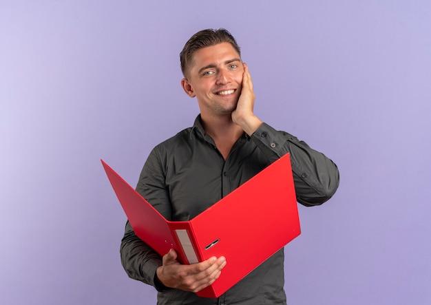 Jeune homme beau blond souriant détient le dossier de fichiers et met la main sur le visage isolé sur fond violet avec espace copie