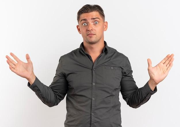 Jeune homme beau blond surpris tient les mains ouvertes isolé sur fond blanc avec espace copie