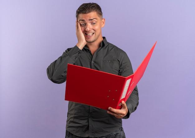 Jeune homme beau blond surpris tient et regarde le dossier de fichiers isolé sur fond violet avec espace de copie