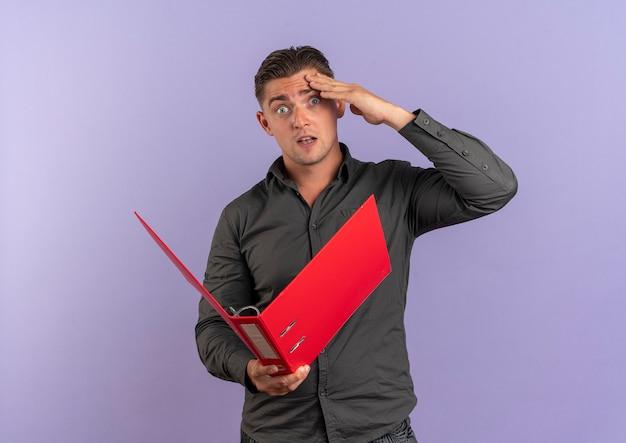 Jeune homme beau blonde surpris met la main sur la tête et détient le dossier de fichiers isolé sur fond violet avec espace de copie
