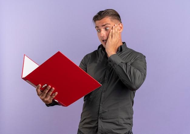 Jeune homme beau blonde surpris met la main sur le visage et regarde le dossier de fichiers isolé sur fond violet avec espace de copie