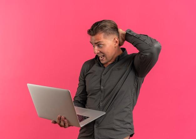 Jeune homme beau blonde surpris tient le cou derrière et regarde un ordinateur portable isolé sur fond rose avec copie espace