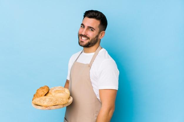 Jeune homme beau boulanger isolé regarde de côté souriant, gai et agréable.
