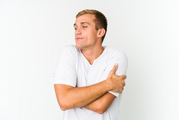 Jeune homme beau caucasien étreint, souriant insouciant et heureux.
