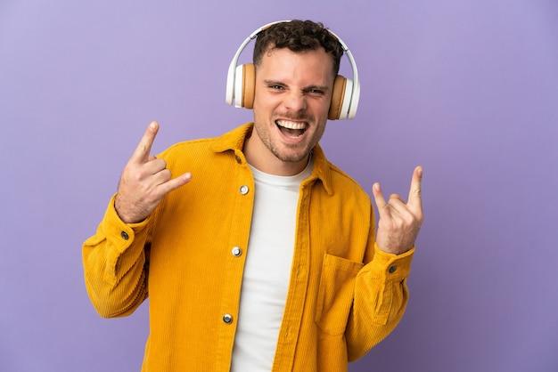 Jeune homme beau caucasien isolé écoute de la musique faisant un geste rock