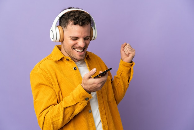 Jeune homme beau caucasien isolé écouter de la musique avec un mobile et chanter