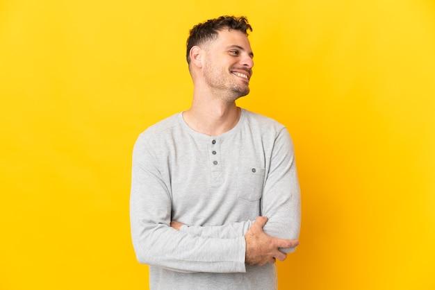 Jeune homme beau caucasien isolé sur fond jaune à côté