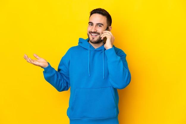 Jeune homme beau caucasien isolé sur fond jaune en gardant une conversation avec le téléphone mobile avec quelqu'un