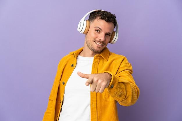 Jeune homme beau caucasien isolé sur un mur violet à l'écoute de la musique