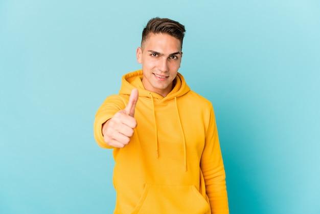 Jeune homme beau caucasien isolé souriant et levant le pouce vers le haut