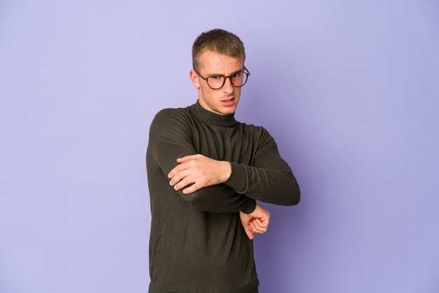 Jeune homme beau caucasien massant le coude, souffrant après un mauvais mouvement.